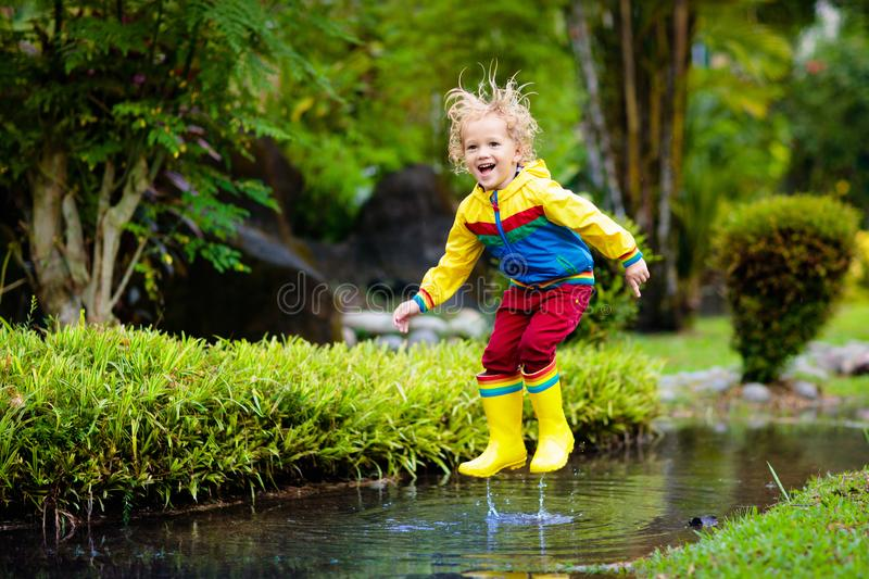Child playing in puddle. Kids jump in autumn rain stock image