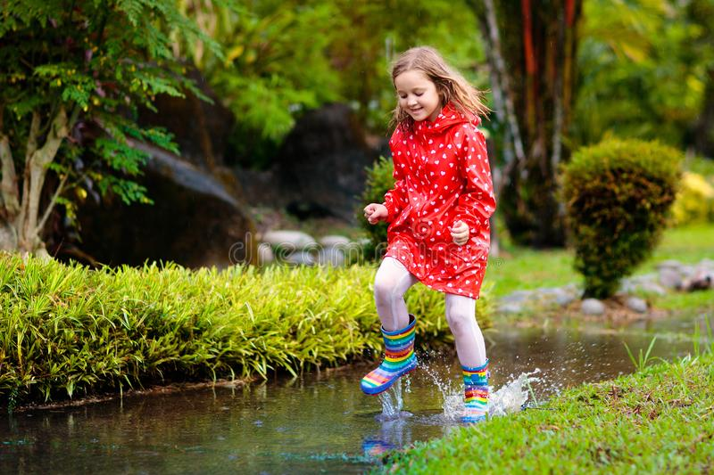 Child playing in puddle. Kids jump in autumn rain royalty free stock photo