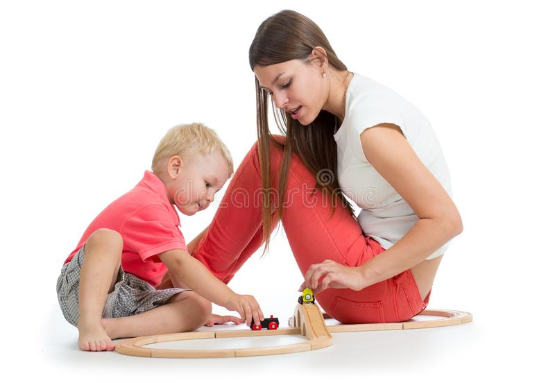 Child playing with railway toys on floor, isolated on white. Mother helps to son royalty free stock images