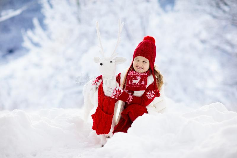 Child playing with reindeer in snow on Christmas vacation. Winter outdoor fun. Kids play in snowy park on Xmas eve. Little girl in stock photography