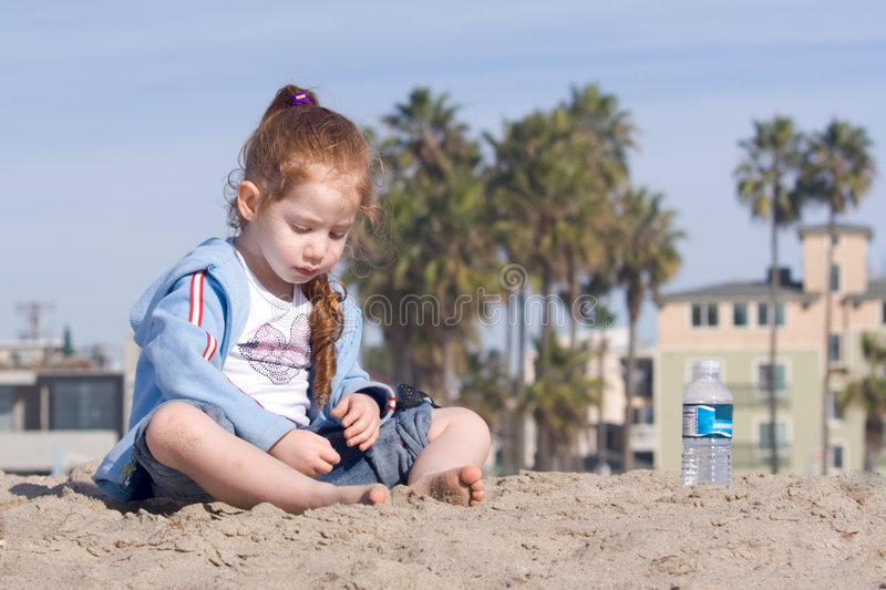 Child playing with sand on a beach stock image
