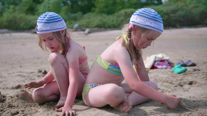 Two girls play on the beach making sand figures. Hot summer day. Family holidays by the sea royalty free stock images