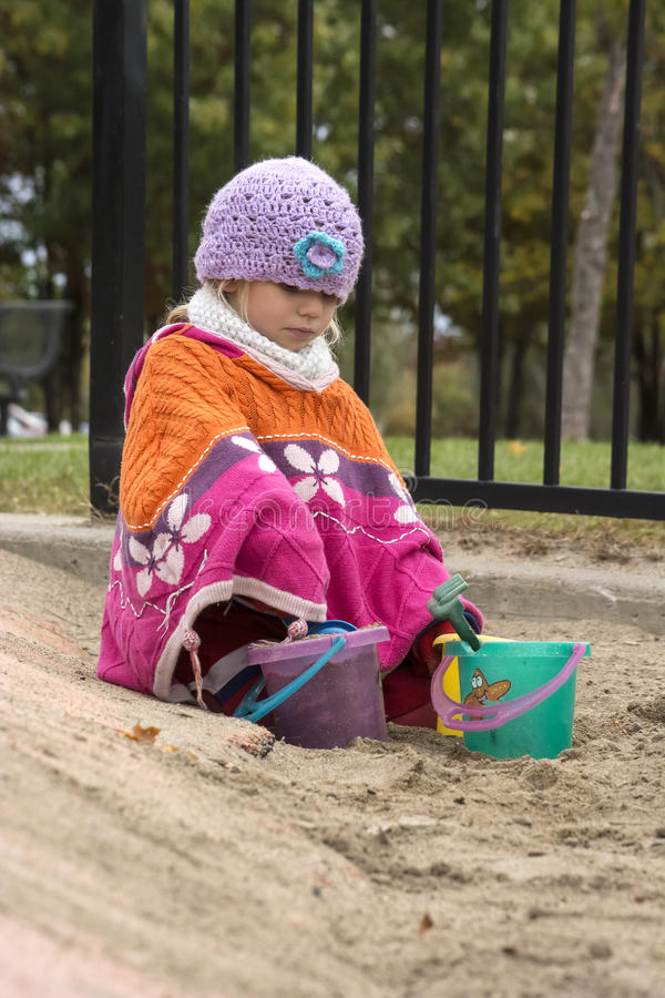 Child playing in the sand. A four years old blond girl child, looking very serious, is playing with buckets and shovels in sand box, she is dressed with bright royalty free stock images