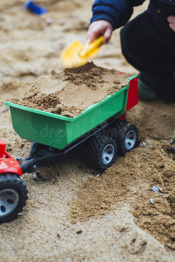 Child Playing Sand With Shovel and Truck Toy royalty free stock images