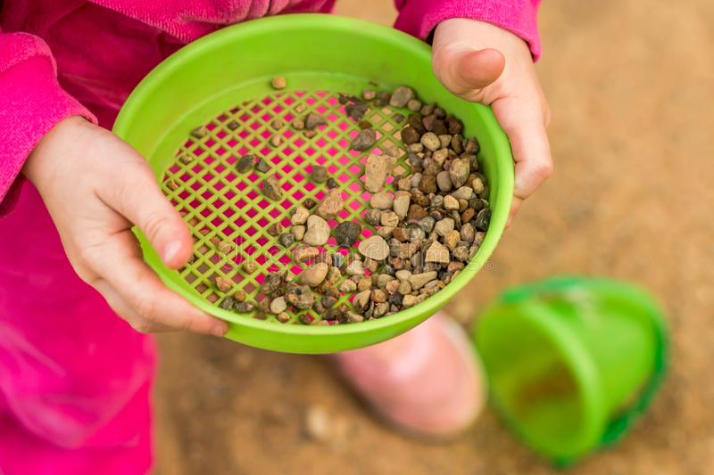 The child is playing in the sandbox. Children`s hands. stock photography