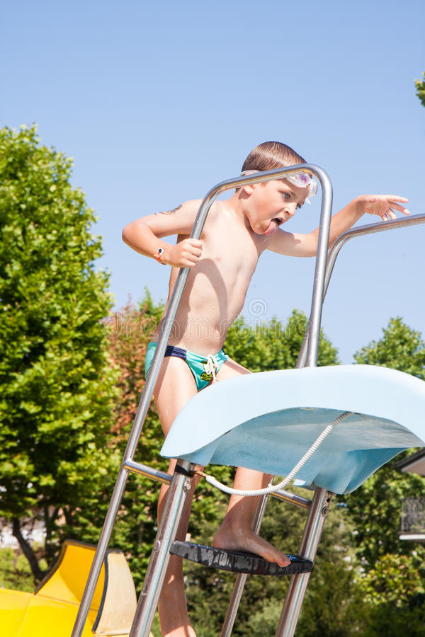 Child playing with the slide in the pool. Happy child playing with the slide in the pool royalty free stock photos