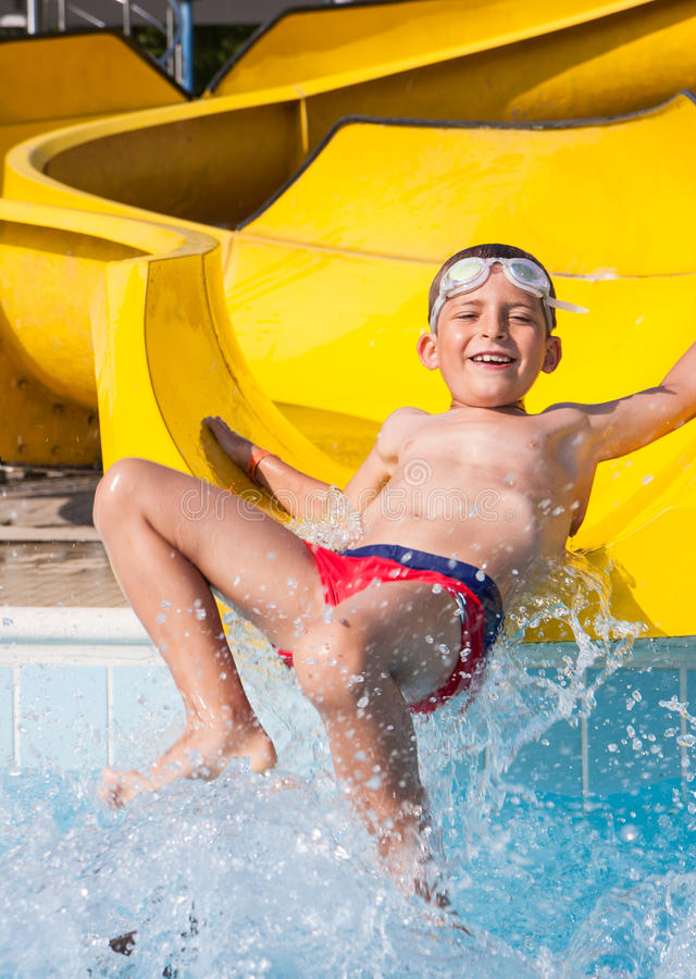 Child playing with the slide in the pool. Happy child playing with the slide in the pool stock photos