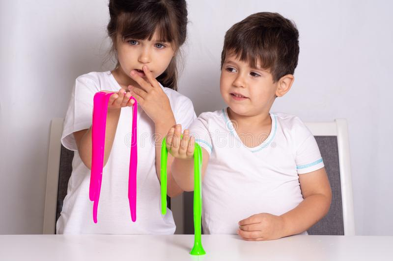 Child playing with slime. Kids squeeze and stretching slime. royalty free stock image