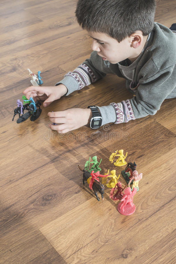 Child playing with small toys. Child playing with small vintage toys on the floor stock photography
