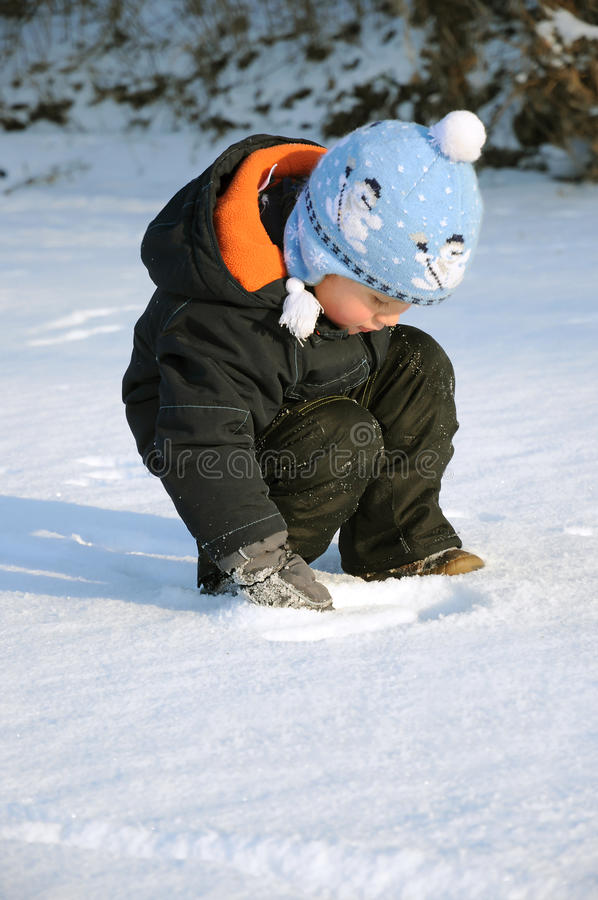 Child playing on snow. Little child playing on snow field, making a picture royalty free stock photo