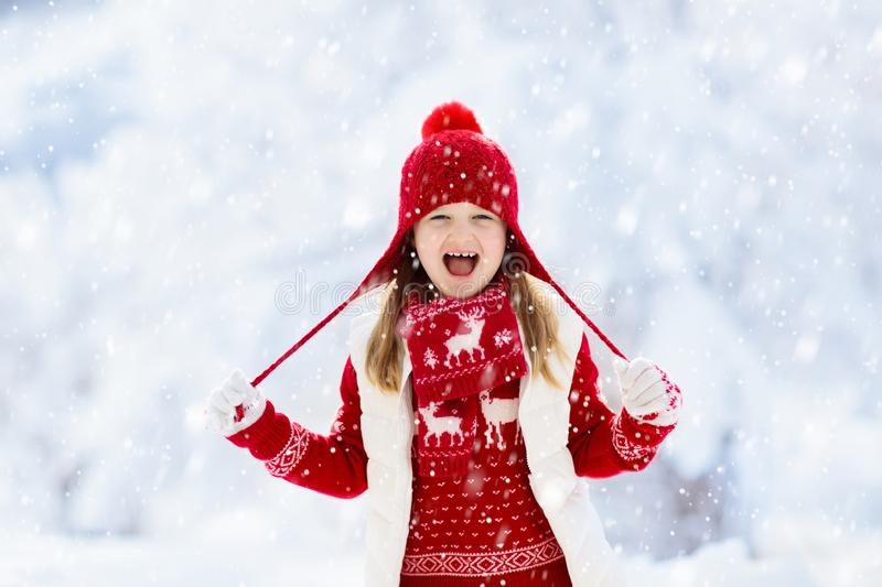 Child playing in snow on Christmas. Kids in winter stock photo