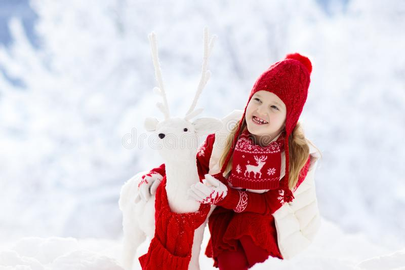 Child playing in snow on Christmas. Kids in winter royalty free stock photography