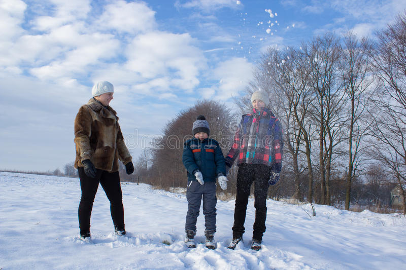 Child playing in snow with mum. Winter outdoors boy with his mother and aunt stock images