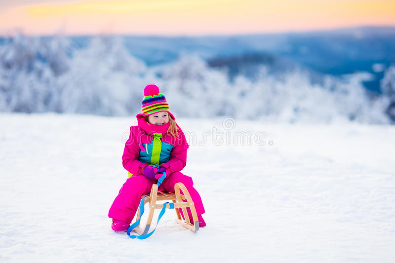 Child playing in snow on sleigh in winter park. Little girl enjoying a sleigh ride. Child sledding. Toddler kid riding a sledge. Children play outdoors in snow stock image