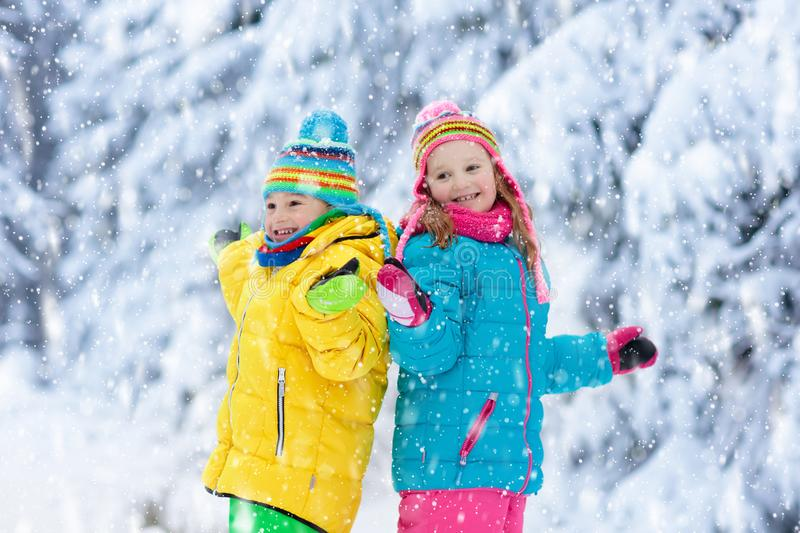 Child playing with snow in winter. Kids outdoors stock photo