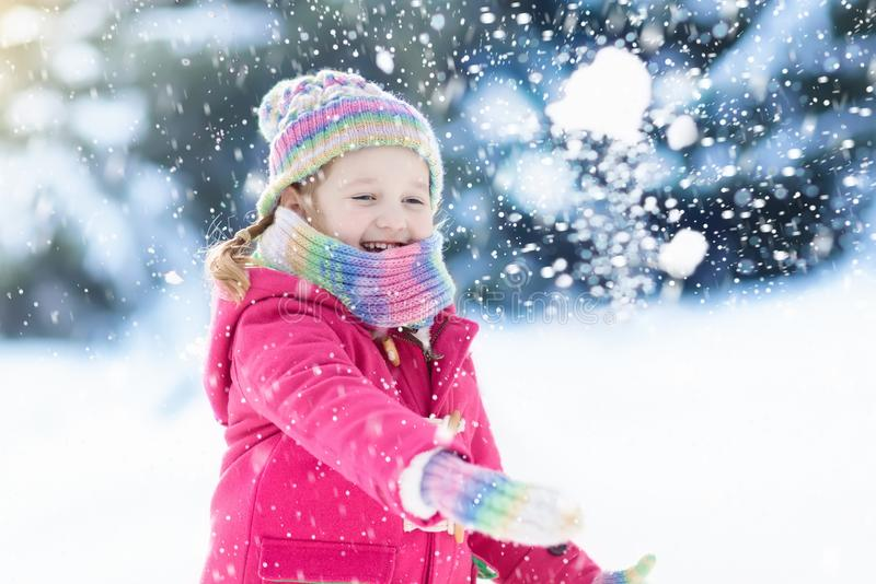Child playing with snow in winter. Kids outdoors. Child playing with snow in winter. Little girl in colorful jacket and knitted hat catching snowflakes in stock images