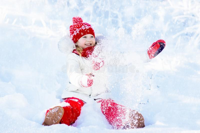 Child playing with snow in winter. Kids outdoors. Child playing with snow in winter. Little girl in colorful jacket and knitted hat catching snowflakes in stock photos