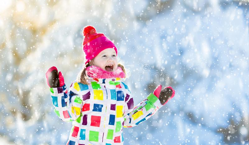 Child playing with snow in winter. Kids outdoors stock images