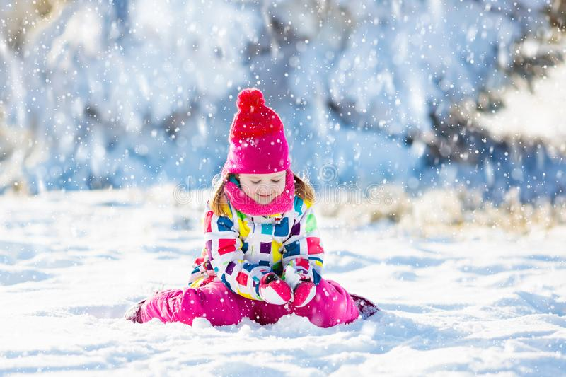 Child playing with snow in winter. Kids outdoors royalty free stock photography