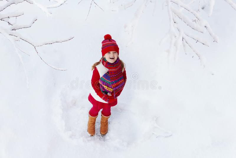 Child playing with snow in winter. Kids outdoors royalty free stock photo