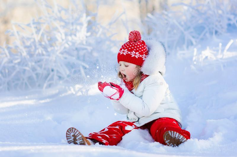 Child playing with snow in winter. Kids outdoors. royalty free stock image