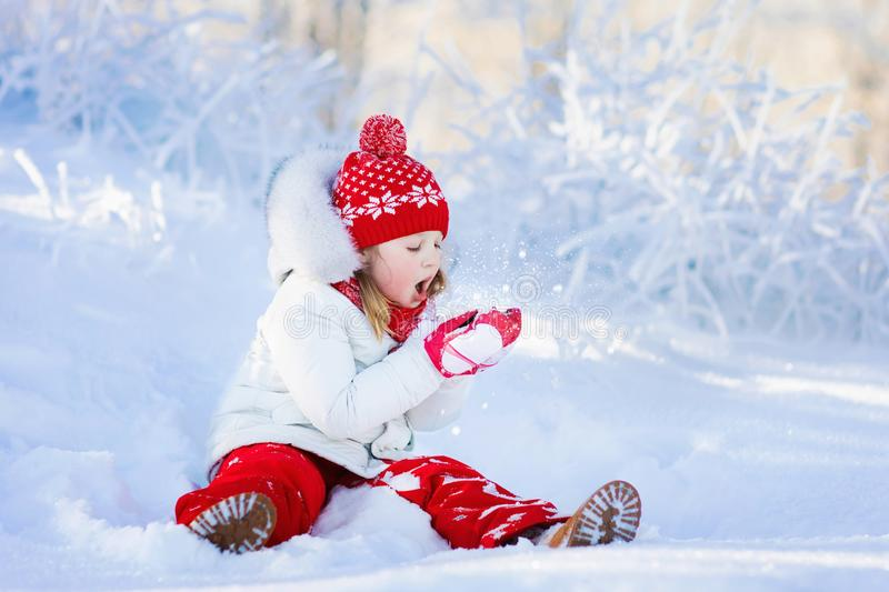 Child playing with snow in winter. Kids outdoors. Child playing with snow in winter. Little girl in colorful jacket and knitted hat catching snowflakes in royalty free stock photo