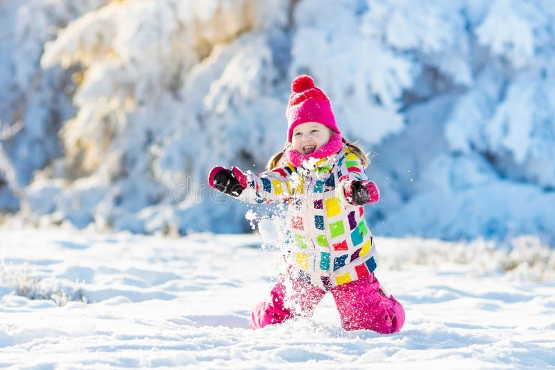 Child playing with snow in winter. Kids outdoors. stock image