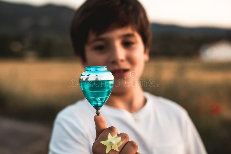 Child playing spinning top. Concept of happy playing children. Kid playing spinning top.Concept of happy playing children royalty free stock image
