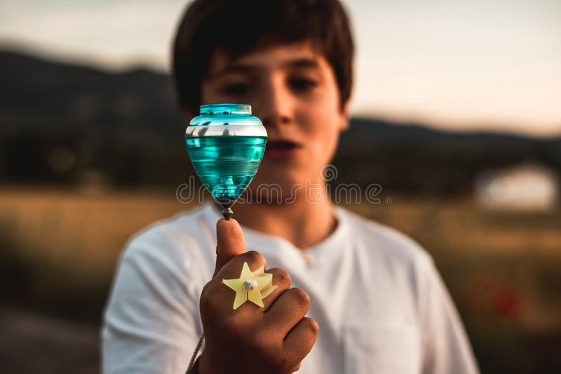 Child playing spinning top. Concept of happy playing children. Kid playing spinning top.Concept of happy playing children royalty free stock photo