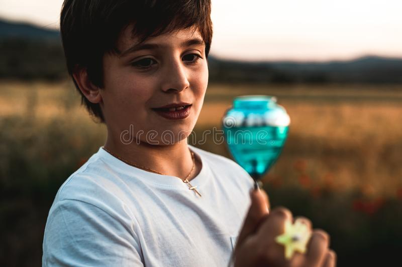 Child playing spinning top. Concept of happy playing children. Kid playing spinning top.Concept of happy playing children stock photography