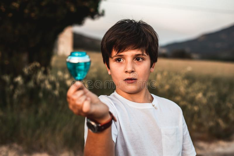 Child playing spinning top. Concept of happy playing children. Kid playing spinning top.Concept of happy playing children stock image