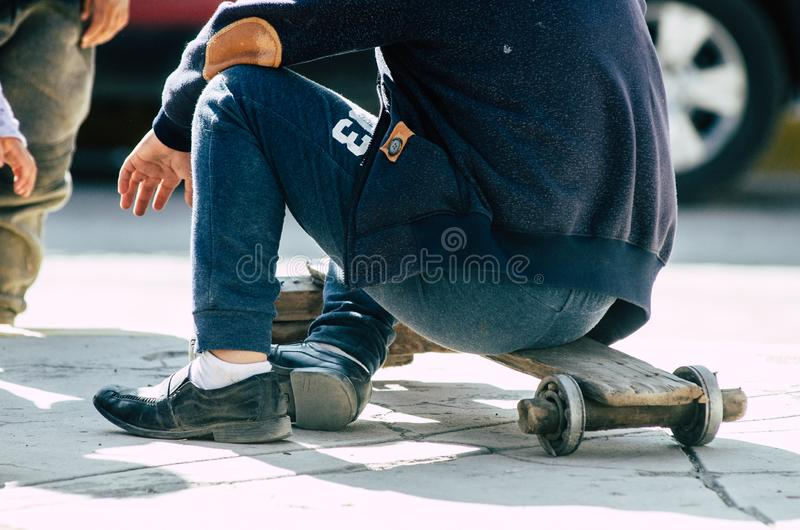 Child playing on the street with a handmade skateboard royalty free stock photo