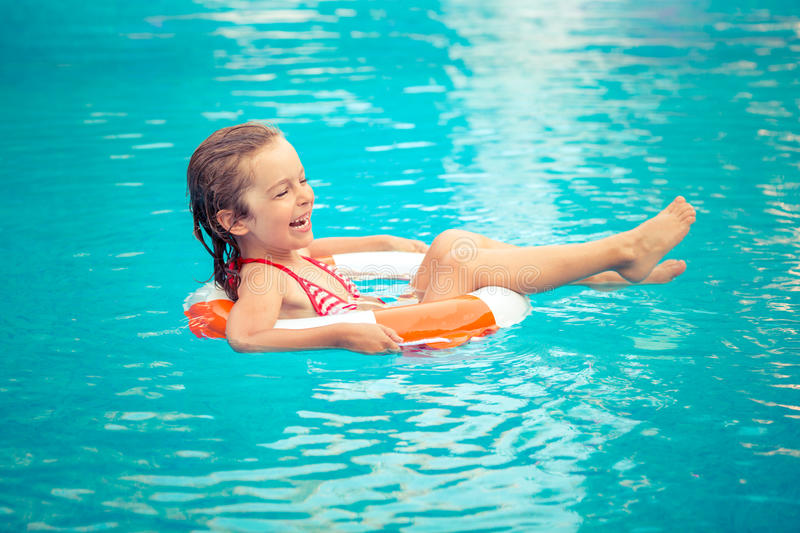 Child playing in swimming pool. Happy child playing in swimming pool. Summer vacation concept royalty free stock images