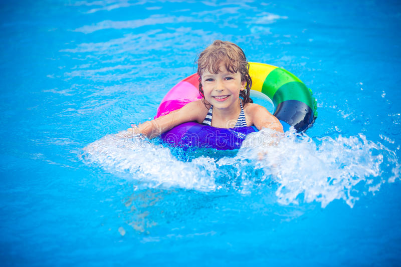 Child playing in swimming pool. Happy child playing in swimming pool. Summer vacation concept royalty free stock image