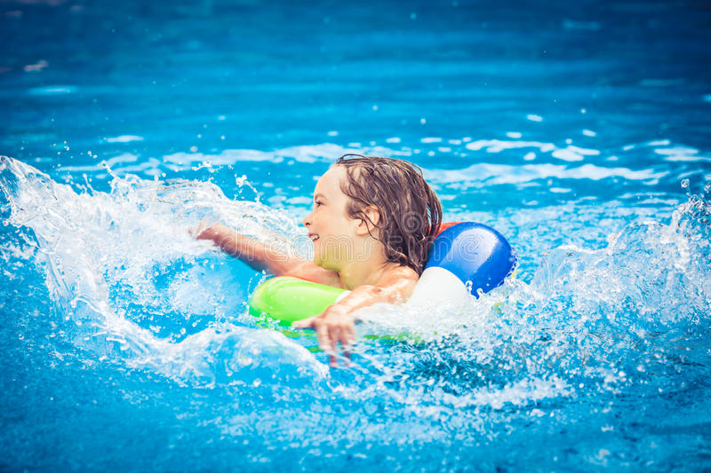 Child playing in swimming pool. Happy child playing in swimming pool. Summer vacation concept stock photography