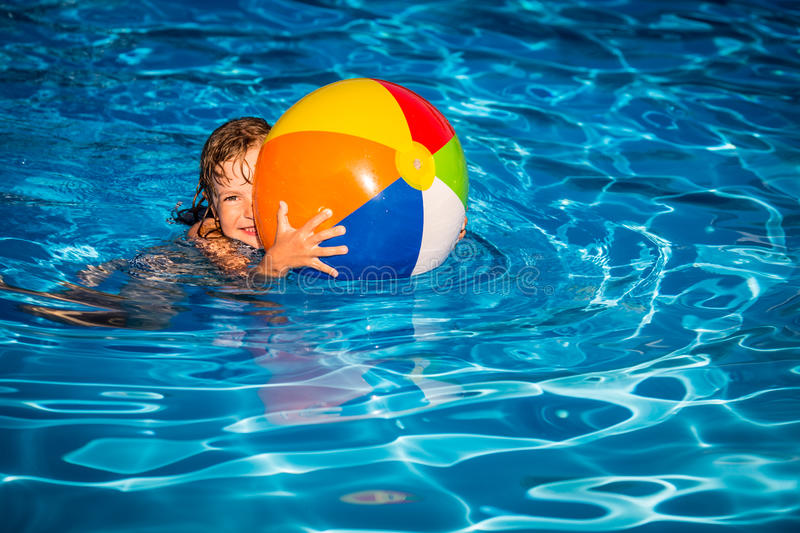 Child playing in swimming pool. Happy child playing in swimming pool. Summer vacation concept royalty free stock photography