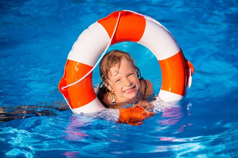 Child playing in swimming pool. Happy child playing in swimming pool. Summer vacation concept stock photos