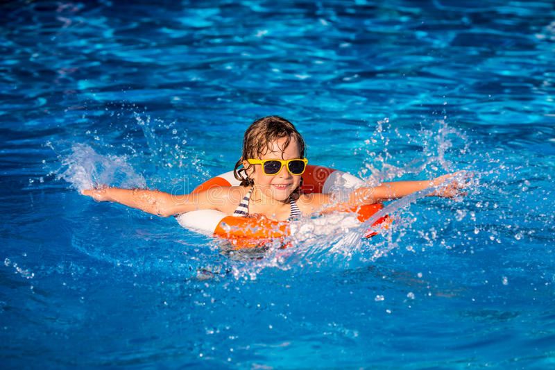 Child playing in swimming pool. Happy child playing in swimming pool. Summer vacation concept stock image
