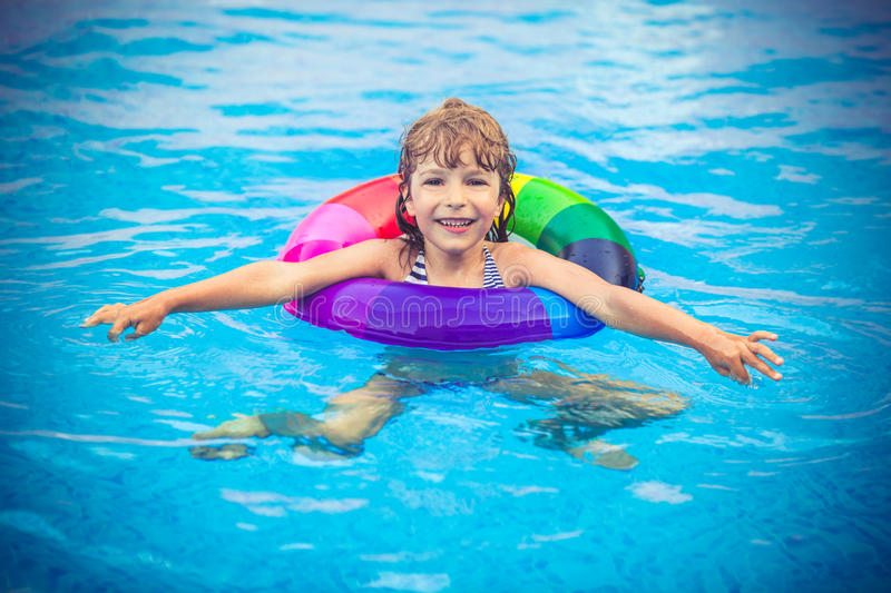 Child playing in swimming pool. Happy child playing in swimming pool. Summer vacation concept royalty free stock photos
