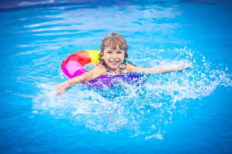 Child playing in swimming pool. Happy child playing in swimming pool. Summer vacation concept stock photo