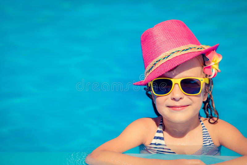 Child playing in swimming pool. Portrait of hipster child in swimming pool. Summer vacation concept stock image