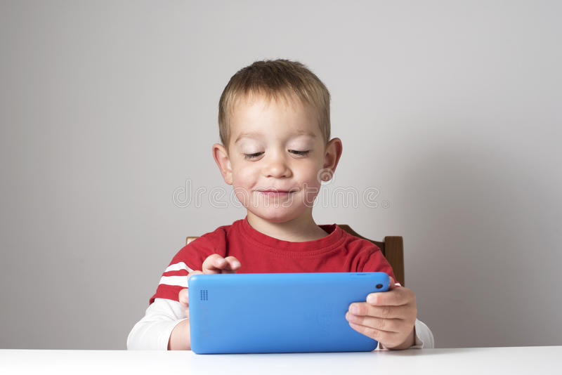 Child playing with tablet. Happy boy in red t shirt playing with blue tablet on plain grey background. Studio shot, horizontal layout with copy space royalty free stock photography
