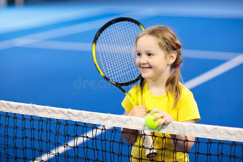 Child playing tennis on indoor court. Little girl with tennis racket and ball in sport club. Active exercise for kids. Summer activities for children. Training stock photos