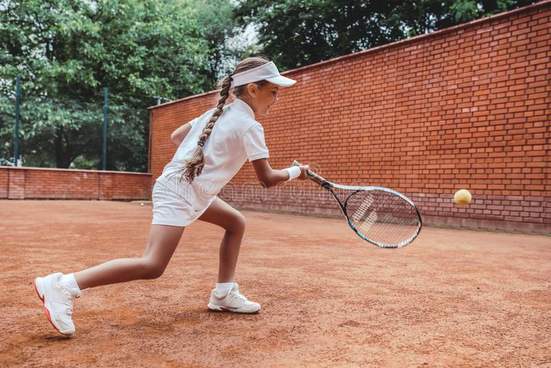 Child playing tennis on outdoor clay court. Full length shot of a tanned little girl on tennis court. Girl child playing tennis. Against the wall. Summer stock image