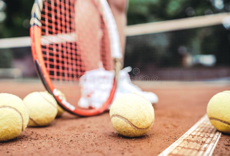 Child playing tennis on outdoor court. Cropped image of child legs on tennis court. Closeup of tennis ball, racket and shoes. royalty free stock photos