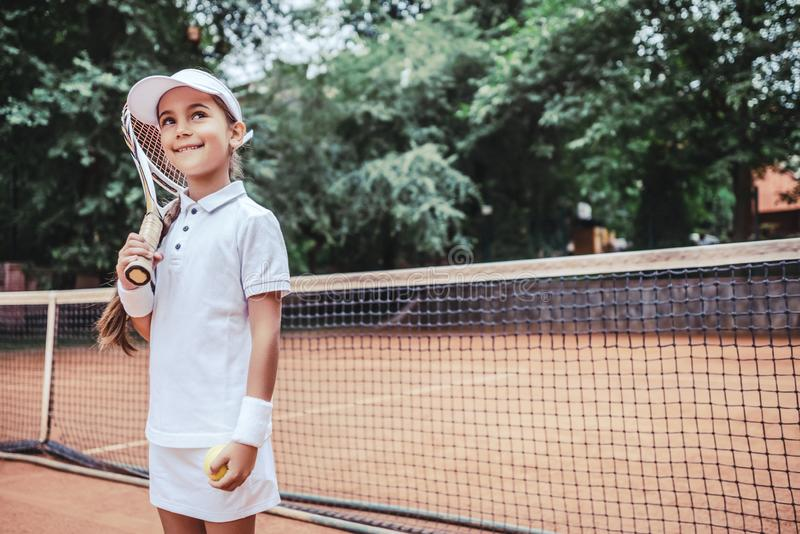 Child playing tennis on outdoor court. Little girl with tennis racket and ball in sport club royalty free stock photo