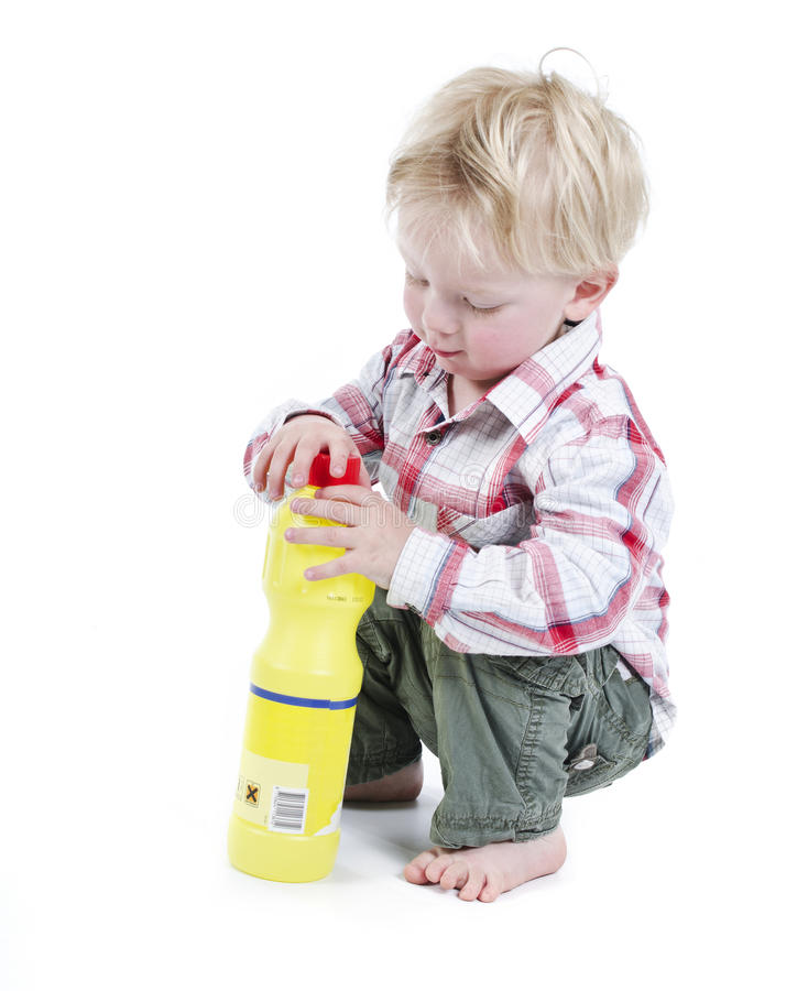 Child playing with toxic cleaner. Materials no adults supervision stock photography
