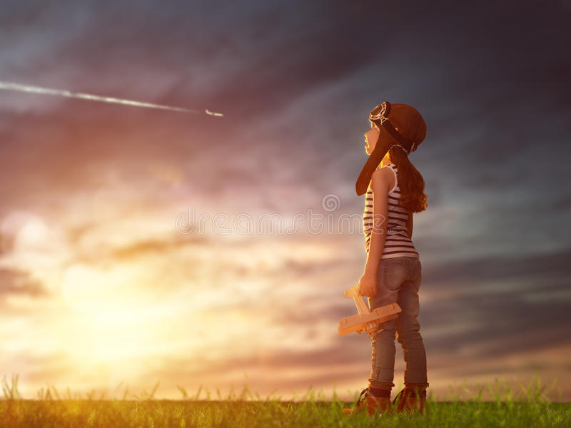 Child playing with toy airplane. Dreams of flight! child playing with toy airplane against the sky at sunset royalty free stock photo