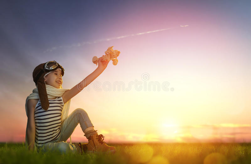 Child playing with toy airplane. Dreams of flight! child playing with toy airplane against the sky at sunset stock images
