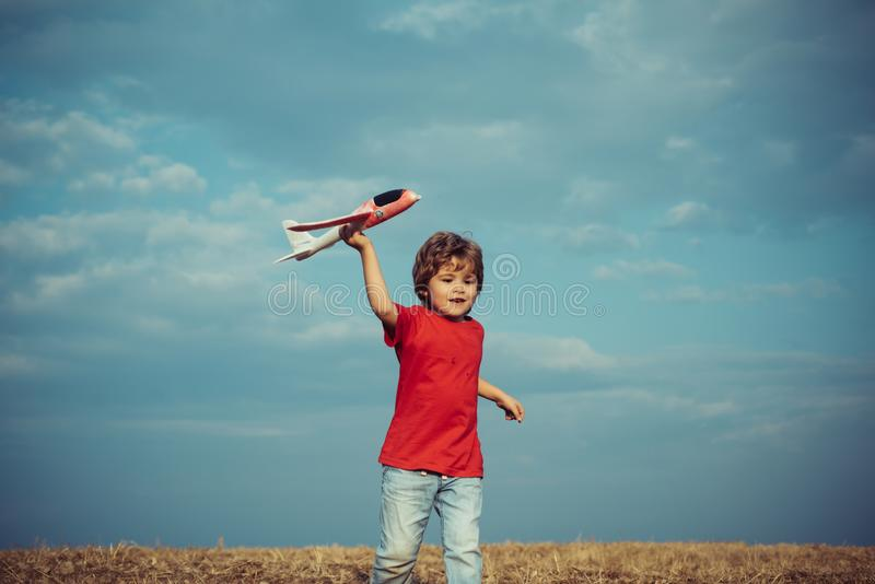 Child playing with toy airplane over meadow having fun and smiling. Childhood on countryside. Cute child playing with royalty free stock photos